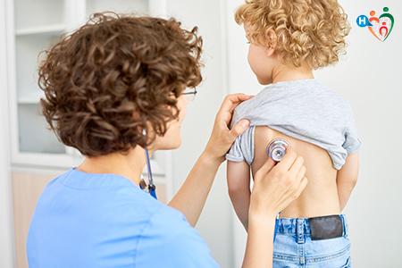 Immagine che mostra un pediatra nell'atto di visitare un bambino