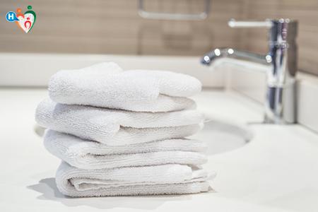 Immagine che mostra degli asciugamani bianchi risposti sopra al piano del lavabo nel bagno