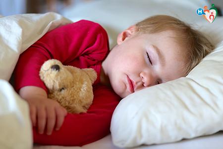 Immagine che mostra un bambino che dorme nel suo letto mentre stringe a sé un orsacchiotto
