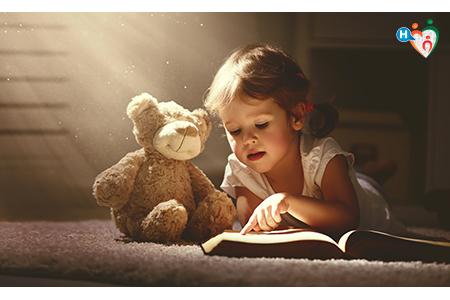 Immagine che mostra un bambini sdraiato per terra in un ambiente buio, come una soffitta, mentre legge un libro al suo amico peluches