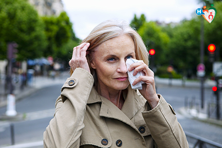 foto che mostra una donna nell'atto di asciugarsi gli occhi mentre lacrimano in preda a una congiuntivite allergica