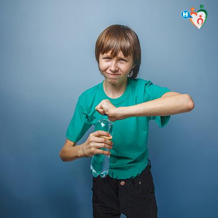 immagine di un bambino mentre si sforza di aprire una bottiglia dell''acqua chiusa