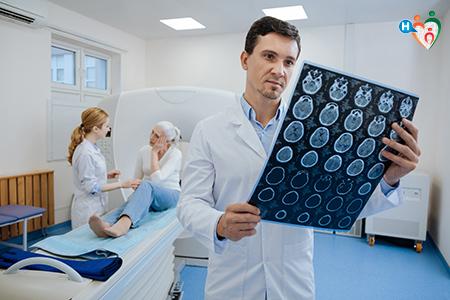 immagine che mostra un medico mentre legge i risultati della risonanza magnetica fatti da un'anziani, assistita da una infermiera.