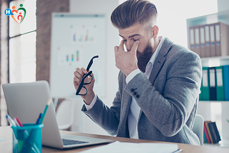 Immagine che mostra un giovane al lavoro davanti al computer mentre si sfrega gli occhi, dopo essersi tolto gli occhiali