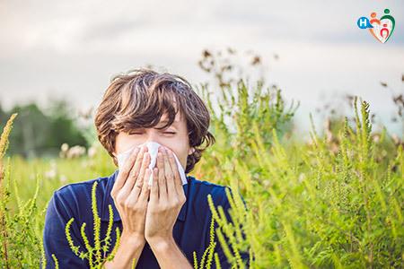 immagine che mostra un ragazzo che si soffia il naso in preda all'allergia