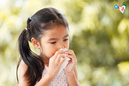 immagine che mostra una bambina mentre si soffia il naso con un fazzoletto usa e getta