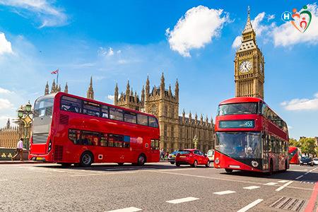 Immagine che mostra due pullman rossi tipici della città di Londra che passano vicino a Westminster