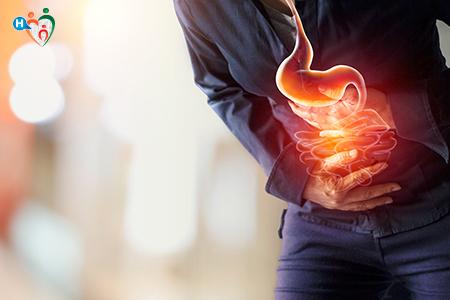 Immagine che mostra un uomo con il dolore allo stomaco piegato in due