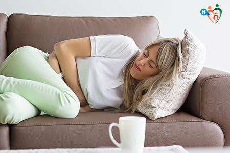 Immagine che mostra una donna rannicchiata sul divano in preda ai dolori allo stomaco